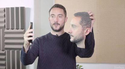 El periodista de 'Forbes' Thomas Brewster prueba el sistema de reconocimiento facial de varios móviles con una representación de su cara impresa en 3D.