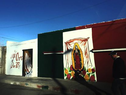 Un mural con la virgen de Guadalupe sobre la bandera mexicana en Ciudad Juárez.