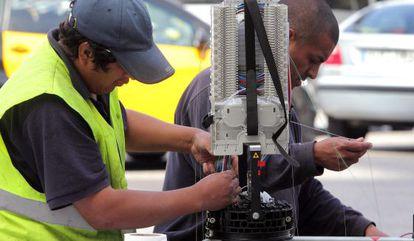 Dos operarios trabajan en la red de fibra optica, en la Gran Via de Barcelona.