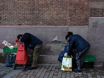 Personas recogiendo la comida que les han entregado en la parroquia de San Ramon Nonato de Madrid, en febrero de 2021.