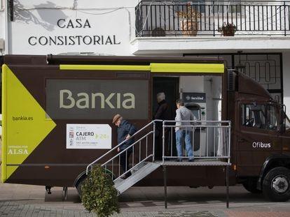 Varios ciudadanos hacen uso de un camión-oficina bancaria en Corpa (Madrid), en 2018.
