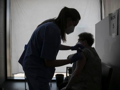 Una enfermera vacuna a una persona en L'Hospitalet de Llobregat.