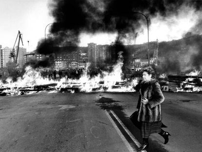 Una mujer con abrigo de piel pasa delante de una barricada en llamas en Bilbao.