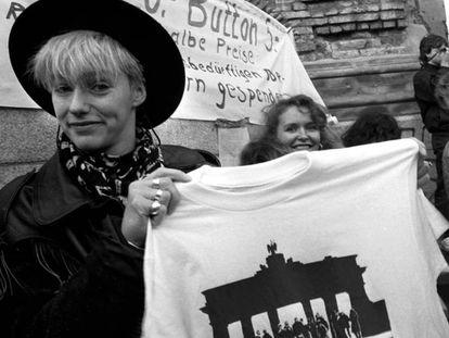Una joven vende camisetas conmemorativas de la caída del Muro.