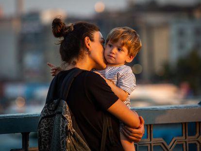 Una mujer besa a un niño.