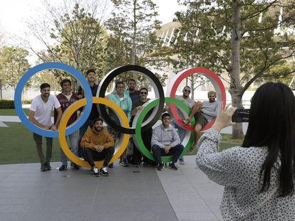 Un grupo de estudiantes uruguayos posan junto a los anillos olímpicos en las afueras del estadio de Tokio (Japón).