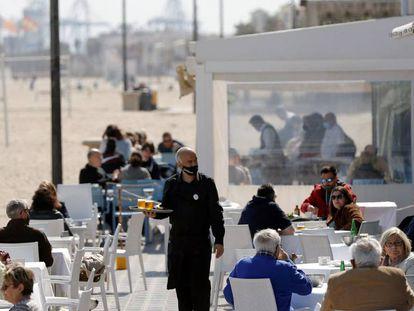 Un camarero atiende las mesas de una terraza en la playa de la Malvarrosa (Valencia), el 15 de marzo.