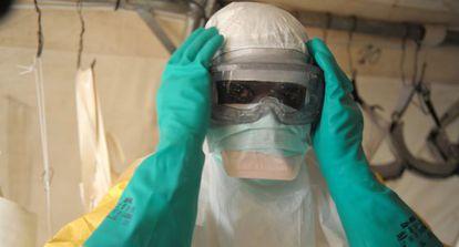 Un médico se coloca el traje de protección para entrar en la sala de aislamiento de Médicos Sin Fronteras en la región de Guekedou.