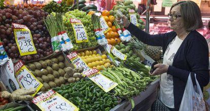 En la imagen, una mujer hace su compra en una fruteria del mercado Maravilla en Madrid.