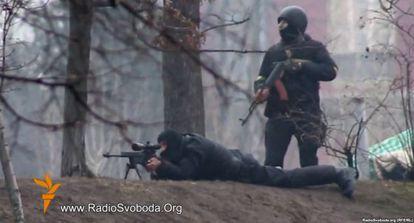 Un policía y un francotirador apuntan a los manifestantes en el centro de Kiev el pasado 20 de febrero.