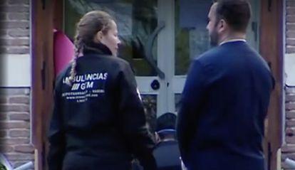 Una trabajadora de Transamed (con el uniforme de GTM, una empresa del mismo grupo) habla con un hombre en la puerta de una residencia durante los días de la operación.