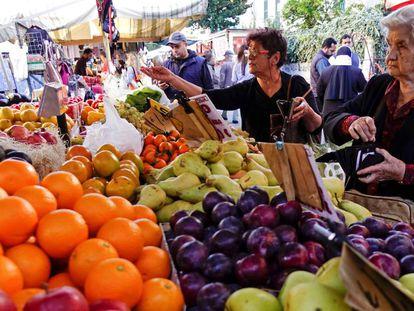 Una mujer compra la fruta en un mercado orgánico.