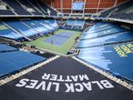 """NEW YORK, NEW YORK - AUGUST 31: """"Black Lives Matter"""" and """"New York Tough"""" signage is seen in Louis Armstrong Stadium as Cori Gauff of the United States serves the ball during her Women's Singles first round match against Anastasija Sevastova of Latvia on Day One of the 2020 US Open at the USTA Billie Jean King National Tennis Center on August 31, 2020 in the Queens borough of New York City.   Al Bello/Getty Images/AFP == FOR NEWSPAPERS, INTERNET, TELCOS & TELEVISION USE ONLY =="""