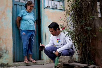 Un voluntario de Mundo Sano inspecciona elementos que pueden almacenar agua de lluvia, donde el mosquito Aedes aegypti pone sus huevos.