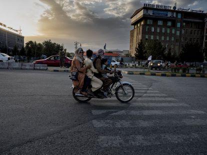 Una familia afgana pasa en moto por una calle de Kabul cerca de un puesto de control de los fundamentalistas.