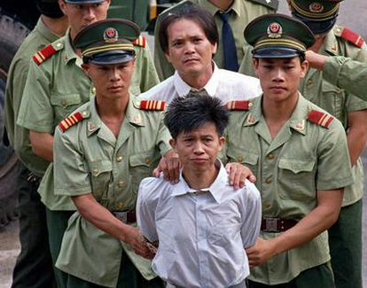 Wang Shijian (delante), de China, y  Wong Tin-soong, de Hong Kong, son conducidos por policías chinos a un estadio en Shenzhen para escuchar el anuncio público de su sentencia a la pena de muerte por tráfico de drogas