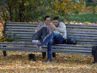 Una pareja de jóvenes observa un móvil en un parque en Kiev.