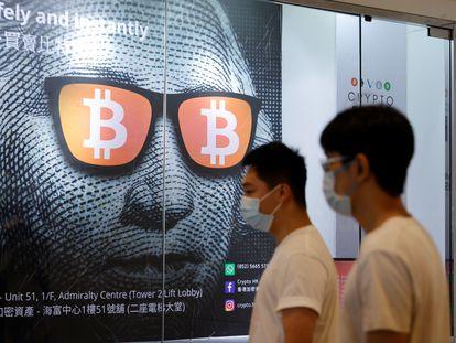 Dos personas pasan frente a un anuncio de Bitcoin en Hong Kong.
