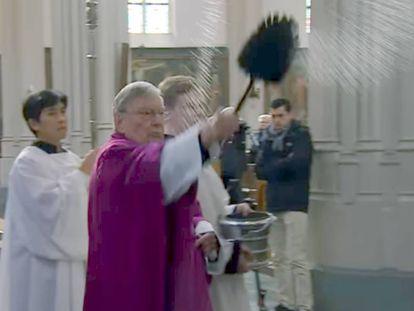 El párroco Jan van Noorwegen rocía con agua bendita el confesionario usado en una de las escenas. La imagen es de un reportaje emitido por la cadena local Omroep Brabant.