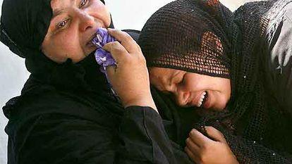 Dos mujeres lloran la muerte de un familiar en la explosión de dos bombas en un campo de fútbol el miércoles en Bagdad.