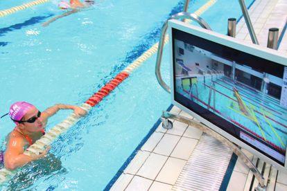 Una nadadora observa detalles sobre su técnica de salida en la piscina  el CAR de Sierra Nevada, en Granada.