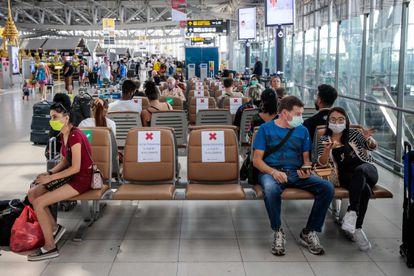 Viajeros llevando máscaras en el aeropuerto de Babkok y respetando la distancia de seguridad que indican los carteles, el 25 de marzo del 2020.
