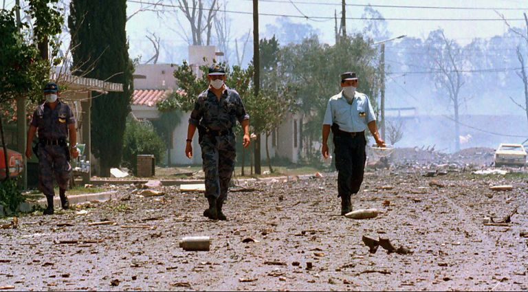 Three policemen walk down a street in Río Tercero (Argentina), after the explosion in November 1995.