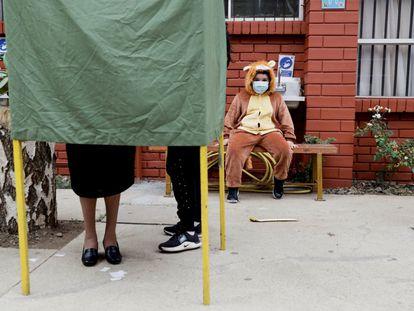 Un niño observa a su madre emitir su voto en Temuco, Chile, el pasado 17 de mayo.