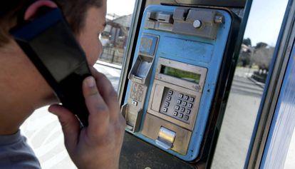 Un joven utiliza una cabina de teléfono