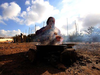 Una mujer siria prepara comida en los alrededores del Centro Temporal de Inmigrantes de Melilla.