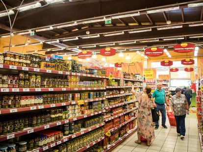 Varios consumidores compran alimentos en un supermercado.