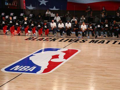 Los jugadores de Phoenix y Washington, ante el logo de la NBA, en un partido en julio de 2020.