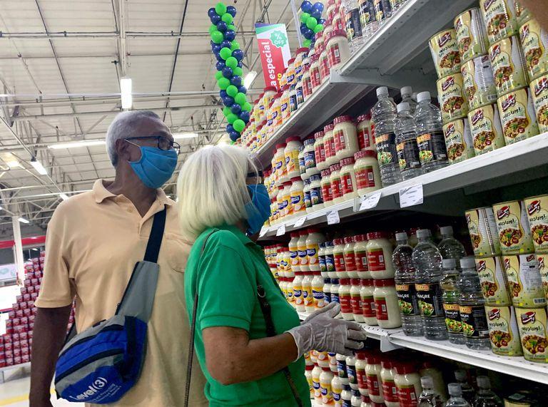 Dos personas con mascarilla compran en un supermercado iraní en Caracas, Venezuela, el 31 de julio.