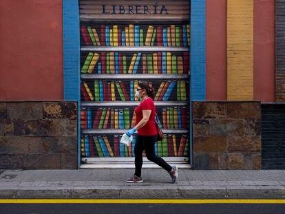 Una mujer pasa por delante de una librería cerrada en Sevilla, en el día internacional del libro.