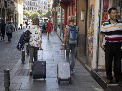 Dos turistas con sus maletas por el centro de Madrid.