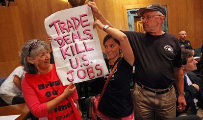 Contrarios a los acuerdos comerciales irrumpen en el Comité de Finanzas del Senado durante una sesión el martes.