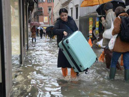 Turistas caminan por las calles inundadas de Venecia este viernes.