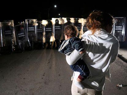Una mujer con un bebé en brazos en un operativo de dispersión de una caravana de migrantes y solicitantes de asilo, en Huixtla, Chiapas. En video, las declaraciones del presidente de México.