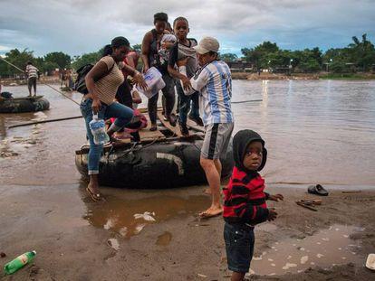 Migrantes provenientes de África y Haití se internan a territorio mexicano este jueves, por las márgenes del rio Suchiate en la linea fronteriza de México y Guatemala.