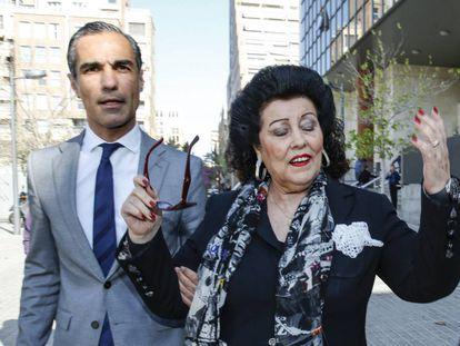 La exdirectora del IVAM, Consuelo Ciscar, junto a su abogado, pide a los medios de comunicación que le dejen pasar, a la salida de los juzgados en Valencia esta mañana.   l