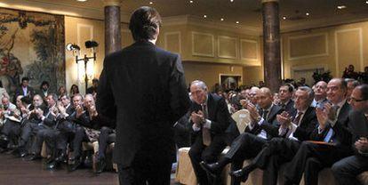 José María Aznar (de espaldas), durante el acto de FAES celebrado ayer. El exdiputado del PP Manuel Pizarro le aplaude en primera fila.