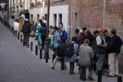Un grupo de personas hace cola para entrar en un comedor social en Madrid