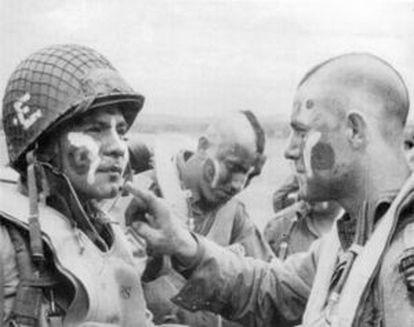Jake McNiece, a la derecha, pone pintura de guerra a un cojpañero la víspera del Día D.