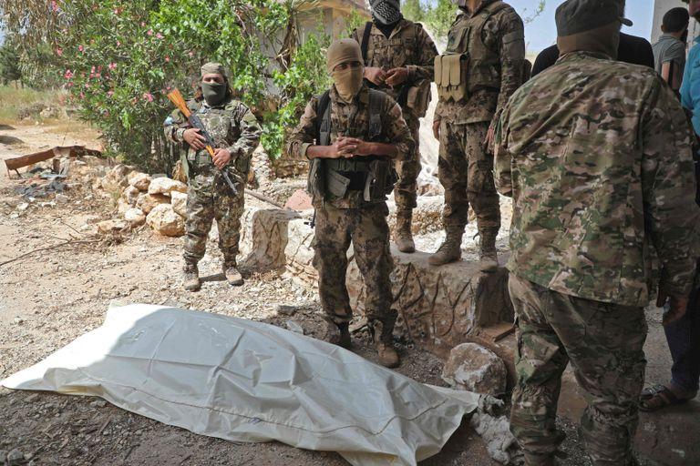 Milicianos rebeldes de Idlib, el sábado en un intercambio de restos de combatientes con el régimen sirio.
