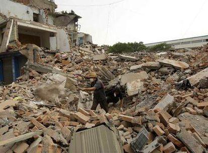 Dos personas buscan cadáveres entre los escombros de casas destruidas.