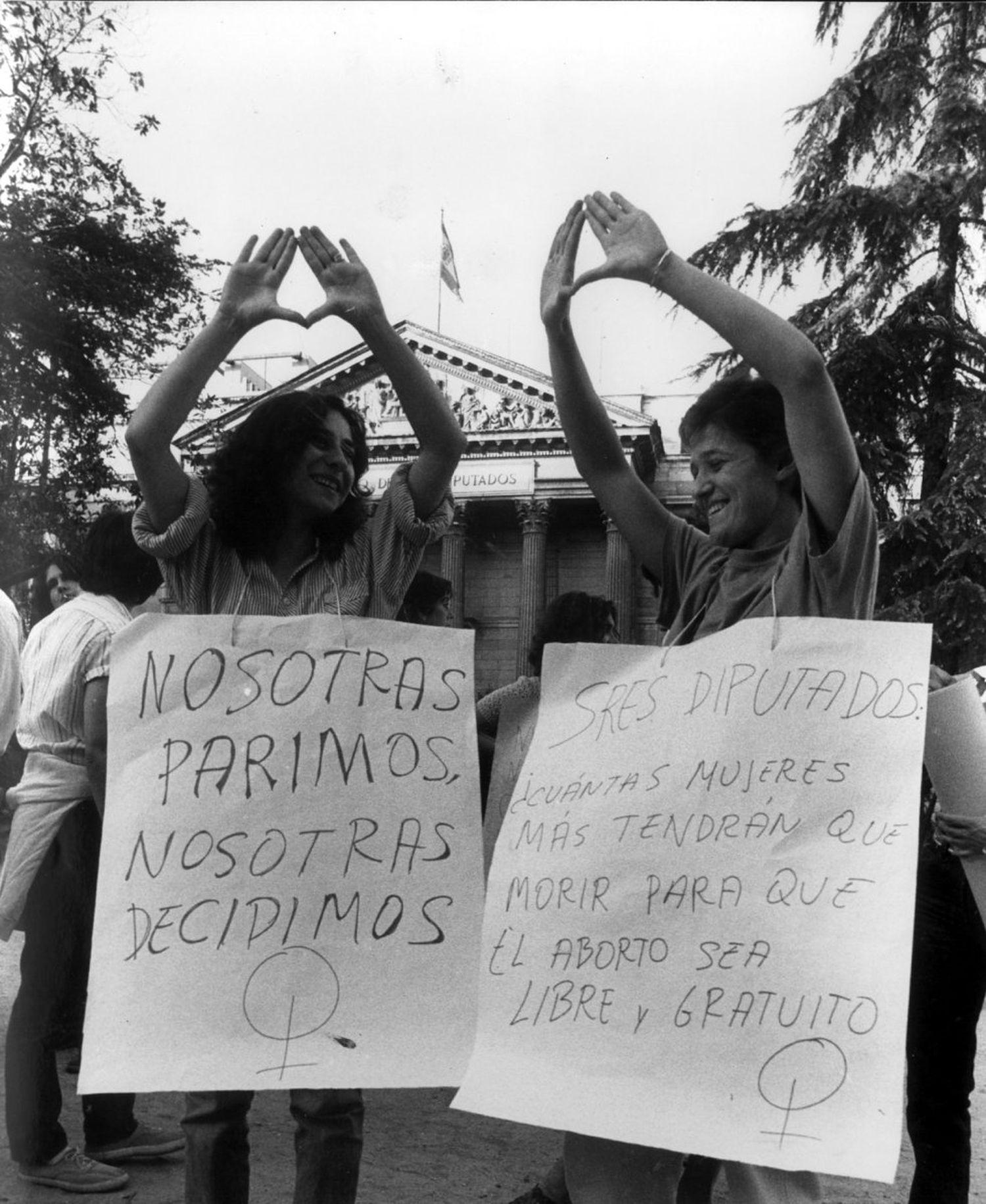 Varias mujeres hacen el signo feminista en una manifestación a favor del aborto libre y gratuito a las puertas del Congreso de los Diputados, durante el debate sobre la despenalización parcial del aborto en casos de violación, grave peligro para la vida de la madre y malformaciones en 1983.
