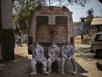 Exhausted workers, who bring dead bodies for cremation, sit on the rear step of an ambulance inside a crematorium, in New Delhi, India, Saturday, April 24, 2021. As India suffers a bigger, more infectious second wave with a caseload of more than 300,000 new cases a day, the country's healthcare workers are bearing the brunt of the disaster. (AP Photo/Altaf Qadri)