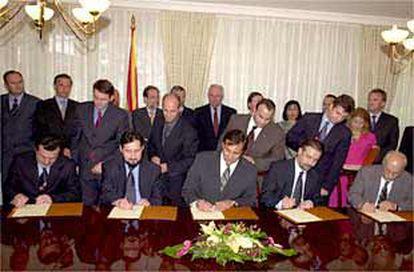 Los líderes eslavos y albaneses de Macedonia (con el presidente Trajkovski, en el centro, y el primer ministro, Georgievski, a su derecha) firman el acuerdo de paz.
