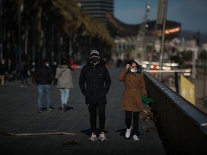 Varias personas con mascarillas pasean por el paseo marítimo de Barcelona.