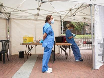 Dos enfermeras esperan a que lleguen personas para vacunar en la plaza Roja de Ciutat Meridiana, en Barcelona.